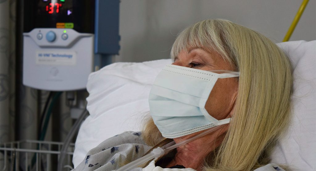 COVID-19 patient receiving Vapotherm therapy while wearing mask